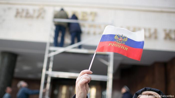 Российский флажок в руках у женщины на фоне здания Крымского парламента