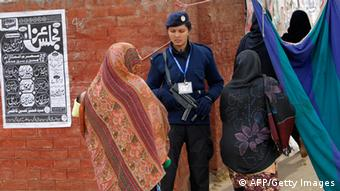 Pakistani Shiite women walk past a policewoman standing guard at the entrance to the Ashura ritual during the holy Islamic month of Muharram in Islamabad