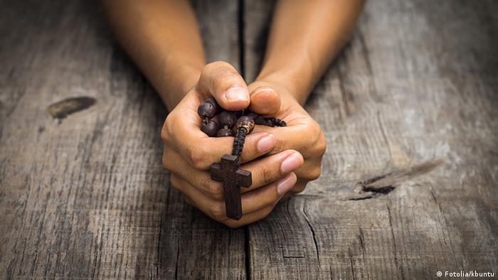 Foto simbólica de una persona con un rosario en la mano.