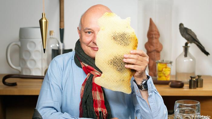 Portrait of artist and designer Rolf Sachs as he holds a bee's honeycomb over half his face Photo: by Byron Slater, copyright Rolf Sachs