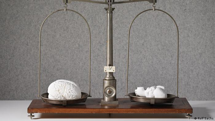 An old-timey scale features a porcelain heart sculpture and a porcelain brain sculpture in balance Photo: by Byron Slater, copyright Rolf Sachs