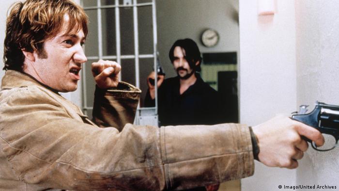 Ein Mann erhebt die Faust. in der anderen Hand hält er eine Pistole. Im Hintergrund steht ein weiterer Mann mit Pistole (Imago/United Archives)