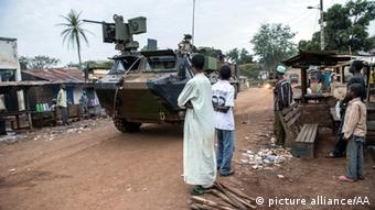 Central African muslim people standing and watching a tank passing by