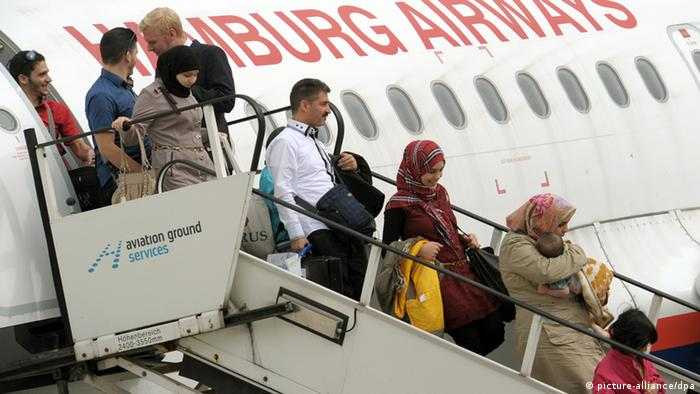 Syrian refugees disembarking from a plane, arriving in Hanover in 2013