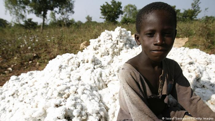 A boy stands in front of a pile of cotton in Ivory Coast