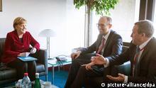 Der ukrainische Übergangsministerpräsident Arseni Jazenjuk (Mitte) trifft sich am Rande des EU-Gipfels im Brüssel mit Bundeskanzlerin Angela Merkel. Am Freitag (21.03.2014) soll der politische Teil des EU-Partnerschaftsabkommens mit der Ukraine unterzeichnet werden (Foto: dpa)