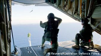 Royal Australian Air Force (RAAF) Loadmasters, Sergeant Adam Roberts (L) and Flight Sergeant John Mancey, launch a 'Self Locating Data Marker Buoy' from a C-130J Hercules aircraft in the southern Indian Ocean during the search for missing Malaysian Airlines flight MH370 in this picture released by the Australian Defence Force March 21, 2014.
