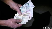 Russian roubles are seen in this photo illustration taken in Moscow, March 7, 2014. Crimea's parliament voted on Thursday to join Russia, and its Moscow-backed government set a referendum in 10 days, in a dramatic escalation of the crisis over the Ukrainian region that drew a sharp riposte from U.S. President Barack Obama. Russian stocks fell and the rouble weakened further after the referendum news. REUTERS/Sergei Karpukhin (RUSSIA - Tags: BUSINESS POLITICS)