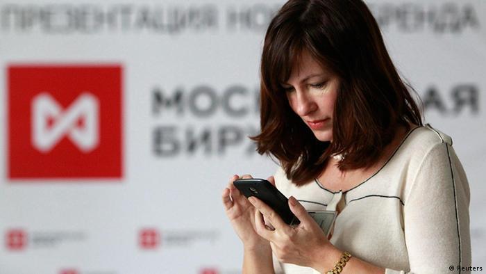 Женщина со смартфоном перед лого Московской биржи