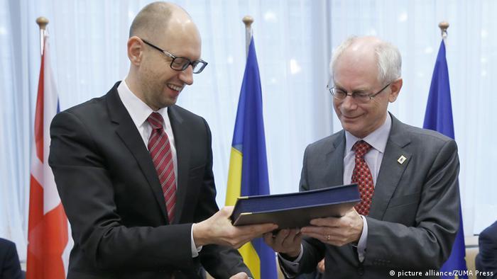 Arseny Jatzenjuk unterzeichnet den politischen Teil des Assoziierungsabkommens mit der EU (Foto: Xinhua)
