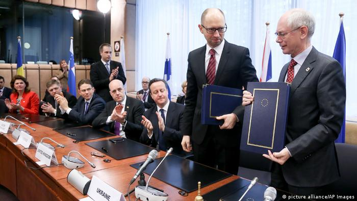 Ukrainian Prime Minister Arseniy Yatsenyuk and European Council President Herman Van Rompuy hold their books during a signing ceremony at an EU summit in Brussels.