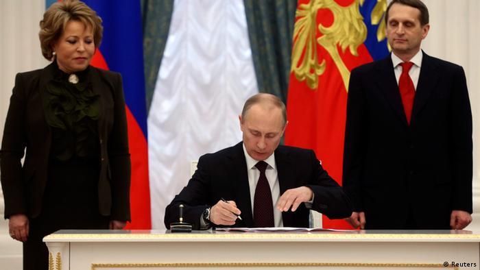 Президент Путин подписывает закон о присоединении Крыма к России.