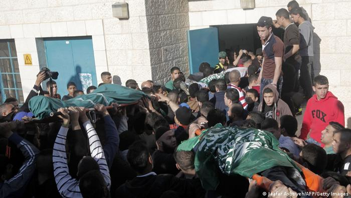 Palestinian men carry the bodies of three people killed by Israeli soldiers