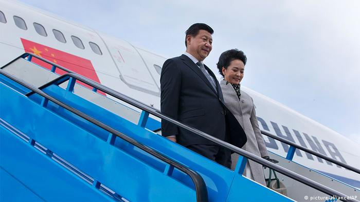 China's President Xi Jinping and his wife Peng Liyuan walk down the stairs from their aircraft prior to being greeted by Dutch King Willem Alexander and Queen Maxima at Schiphol Amsterdam airport, Netherlands, Saturday March 22, 2014.