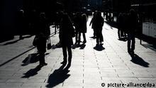 ARCHIV - Im Gegenlicht zeichnen sich Passanten auf einem Gehweg in Dresden als dunkle Silhouetten ab, aufgenommen am 03.01.2012. Droht mit der Ost-Öffnung des Arbeitsmarkts eine Zuwanderungswelle? Die CSU sagt Ja - und will Sozialmissbrauch erschweren. Bulgariens Botschafter spricht von Populismus. Foto: Arno Burgi/dpa (zu dpa Bulgariens Botschafter kritisiert Debatte über Armutszuwanderung vom 31.12.2013) +++(c) dpa - Bildfunk+++