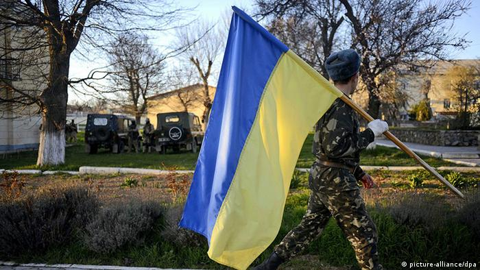 Солдат з українським прапором на воєнній базі Бельбек. Березнь 2014-го
