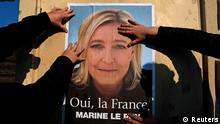 Supporters paste a poster of Marine Le Pen, France's National Front leader, on a wall before a political rally for local elections in Frejus March 18, 2014. The French will go to the polls to cast votes in the two-round 2014 Municipal elections on March 23 and March 30 to elect city mayors and councillors for a six-year term. REUTERS/Eric Gaillard (FRANCE - Tags: POLITICS ELECTIONS TPX IMAGES OF THE DAY)