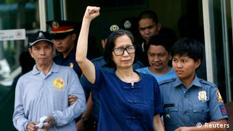 Philippines communist leaders Benito Tiamzon (L) and wife Wilma Austria Tiamzon (C) are escorted by police after they were arrested, in Manila March 23, 2014.