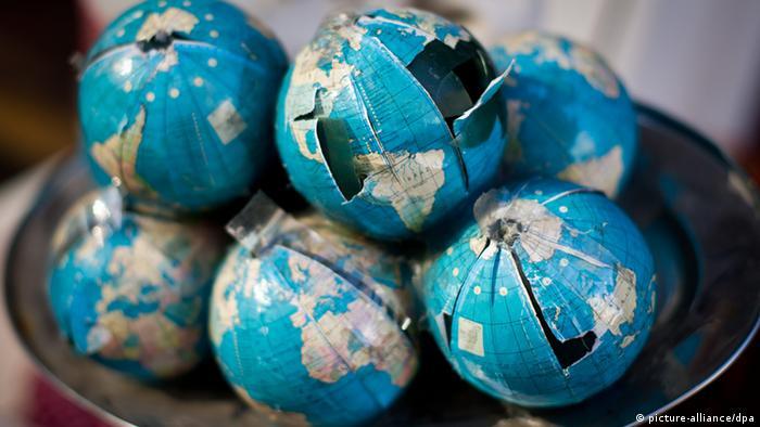 Kleine beschädigte Weltkugeln liegen auf einem Tablett (Foto: O. Spata/dpa).