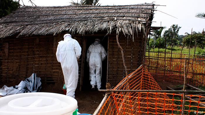 MSF staff entering a hut in Guinea in protective suits