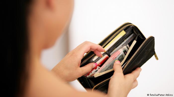 Студентка заглядывает в кошелек