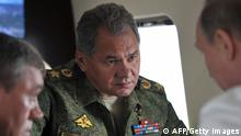 Russian President Vladimir Putin (R), Defense Minister Sergei Shoigu (C) and Chief of General Staff Valery Gerasimov (L) talk as the Russian Army and Navy conduct exercises near the eastern Siberian city of Chita on July 17, 2013. Putin inspected huge military exercises the Russian Army is carrying out near the borders with Japan and China, in one of its biggest shows of force in the Asia-Pacific region of recent years. Thousands of tanks, 160,000 servicemen, 130 aircraft and 70 ships are involved in maneuvers which extend over a vast area from southeastern Siberia on the border with China to Sakhalin Island north of Japan. AFP PHOTO/ RIA-NOVOSTI / ALEXEI NIKOLSKY (Photo credit should read ALEXEI NIKOLSKY/AFP/Getty Images)