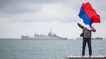 Ein Mann posiert am mit einer Russland-Fahne an der Bucht in Sewastopol, Ukraine. (Foto: dpa)
