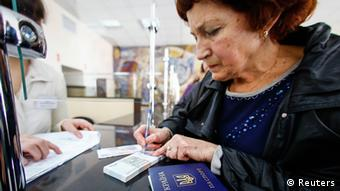 A woman in Crimea receives her pension in Russian rubles at a till (Photo: REUTERS/Shamil Zhumatov)
