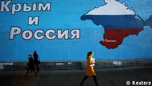 People walk past a mural showing a map of Crimea in the Russian national colours on a street in Moscow March 25, 2014. Russia and the West sought to draw a provisional line under the Ukraine crisis on Tuesday after major industrialised nations warned Moscow of tougher economic sanctions if it goes beyond the seizure of Crimea. The mural reads: Crimea and Russia. REUTERS/Artur Bainozarov (RUSSIA - Tags: POLITICS TPX IMAGES OF THE DAY)