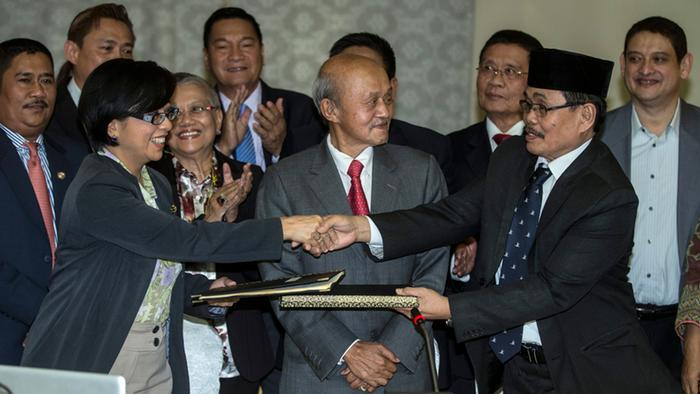 Philippines Government Peace Panel Chairperson, Miriam Coronel-Ferrer (L), shakes hand and exchanges a document with chief negotiator for the Moro Islamic Liberation Front (MILF), Mohagher Iqbal (R), as witnessed by Malaysian Facilitator Abdul Ghafar Tengku Mohamed (C) during the 43rd Government of the Philippines GPH-MILF Exploratory Talks in Kuala Lumpur, Malaysia, 25 January 2014. The Philippines' largest Muslim rebel group agreed to decommission its forces, part of a peace agreement aimed at ending more than four decades of insurgency in the country's troubled south. The agreement on normalization, signed in Kuala Lumpur, calls for Muslim self-rule in parts of the southern Philippines in exchange for a deactivation of rebel forces by the Moro Islamic Liberation Front (MILF).