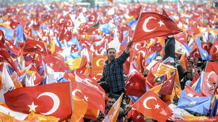 People hold Turkish flags (photo: BULENT KILIC/AFP/Getty Images)