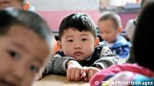 Young Chinese children attend a kindergarten set up for migrant workers, which is marked for demolition, in Beijing on April 26, 2012. Under China's complex residency laws, most migrant workers remain registered in their native towns and villages and do not qualify for the all-important hukou, or household registration permit, in the city where they live, and without this document, their children do not qualify for places in public schools, making the unregistered fee-paying migrant schools their only option. CHINA OUT AFP PHOTO (Photo credit should read STR/AFP/GettyImages)