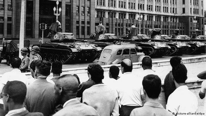 Cidadãos observam tanques diante do Ministério da Guerra em Brasília em 1964