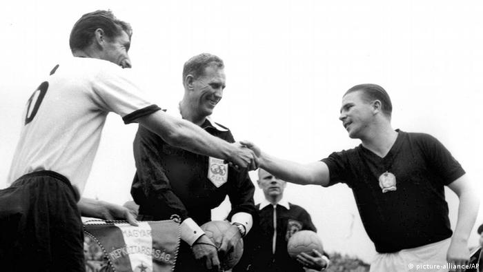 West German captain Fritz Walter and his Hungarian counterpart Ferenc Puskas shake hand pre-match