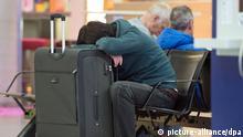 Auf seinen Koffer aufgestützt schläft ein Passagier am 27.03.2014 auf dem Flughafen in Frankfurt am Main (Hessen). Im Tarifstreit des öffentlichen Dienstes haben die Gewerkschaften ihre Warnstreiks in mehreren Bundesländern fortgesetzt. Die Gewerkschaften fordern für die 2,1 Millionen Angestellten von Bund und Kommunen eine Erhöhung der Gehälter um einen Sockelbetrag von 100 Euro und um weitere 3,5 Prozent. Am Flughafen Frankfurt fielen mehrere hundert Flüge aus. Foto: Boris Roessler/dpa