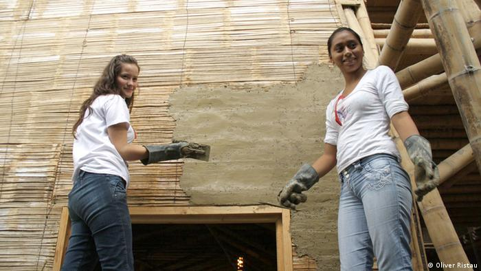 Two girls putting mud on a bamboo wall. (Photo: Oliver Ristau)