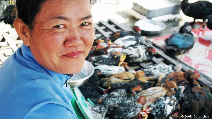 Vendor Ly Mey at her stall at Chhbar Ampov market in Phnom Penh. After the customer picks out the chicken they want, Ly Mey slaughters, plucks and guts it for the customer. Copyright: DW/Robert Carmichael Phnom Penh
