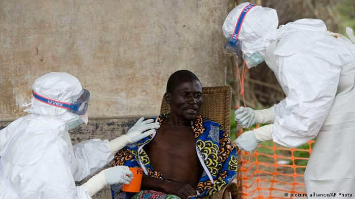 An African man is treated for Ebola by two men in white biohazard suits