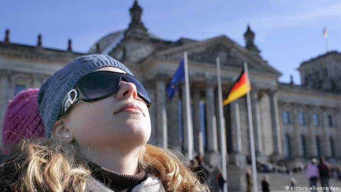 Eine Frau mit Mütze und Sonnenbrille schaut vor dem Berliner Reichstag in den Himmel