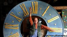 Peter Leonardy, Initiator des Zeitgeist-Forum in Karlsruhe (Baden-Württemberg), steht am 29.03.2013 im Zeitgeist-Uhrenmuseum in Karlsruhe in einem überdimensionalen Ziffernblatt, das um 1870 entstand und an einer Kirche angebracht war. Leonardy deutet mit seinem Armen die Uhrzeit drei Uhr an. In der Nacht vom 30.03.2013 auf den 31.03.2013 wird die Zeit von zwei Uhr eine Stunde - auf drei Uhr - vorgestellt. Foto: Uli Deck/dpa +++(c) dpa - Bildfunk+++