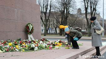Person laying flowers at the Freedom Monument in Riga