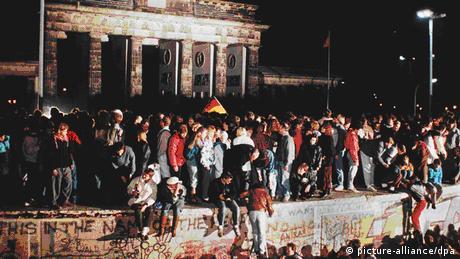 People sitting on Berlin Wall on November 9, 1989