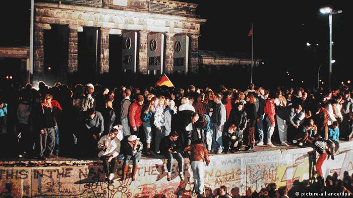 People sitting on Berlin Wall on November 9, 1989 (picture-alliance/dpa)