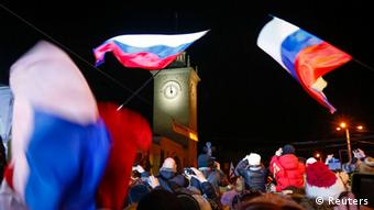 People waving Russian flags at clock tower in Simferopol (Photo: Shamil Zhumatov/REUTERS)