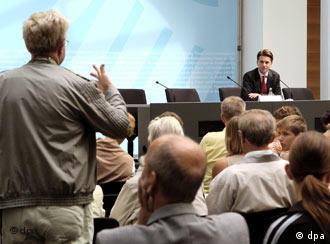 periodistas sentados de espalda en una sala de conferencia, uno de ellos de pie, al fondo está el portavoz del gobierno