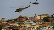 Police helicopters fly over the Mare slum complex during it's occupation in Rio de Janeiro, Brazil, Sunday, March 30, 2014. The Mare complex of slums, home to about 130,000 people and located near the international airport, is the latest area targeted for the government's pacification program, which sees officers move in, push out drug gangs and set up permanent police posts. (AP Photo/Leo Correa)