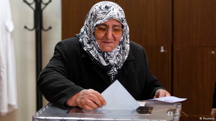 Пожилая турчанка опускает избирательный бюллетень в урну для голосования
