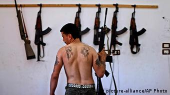 A man with his back to the camera stands before a number of automatic weapons