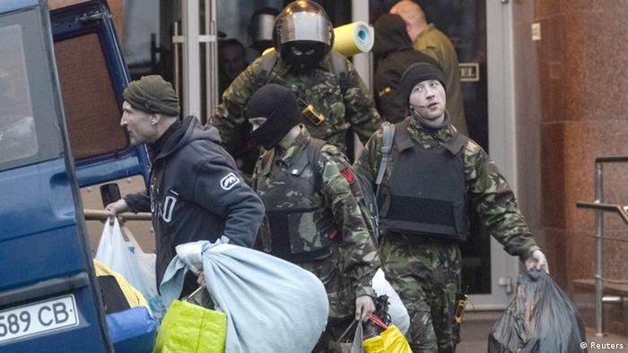 Members of the Ukrainian far-right radical group Right Sector leave their headquarters in Dnipro Hotel as police special forces stand guard in Kiev April 1, 2014.