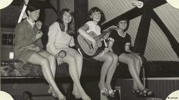 The five girls in the folk band sitting on a balcony.